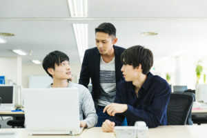 OJT中の若手社員とアドバイスを送る上司と先輩社員
