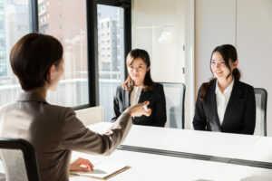 面接官と対峙する2人の求職者