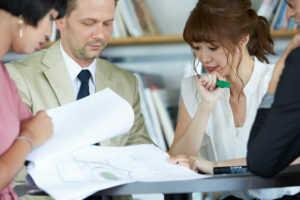 小さな机を囲み資料を開いて打ち合わせをしている男女