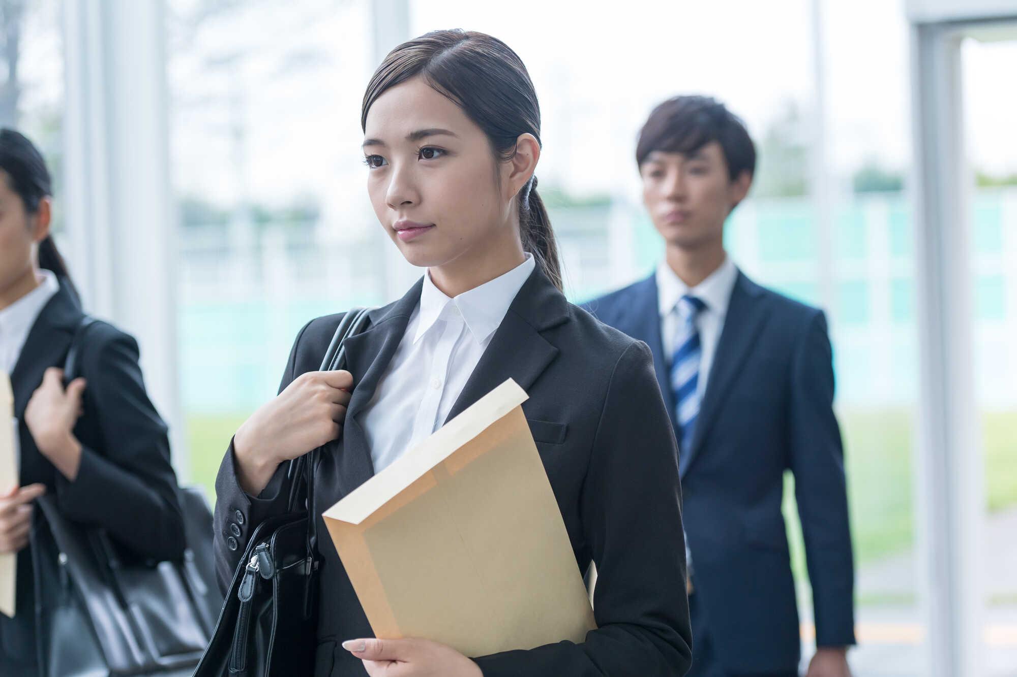 書類を入れた封筒をわきに抱えたリクルートスーツ姿の女性