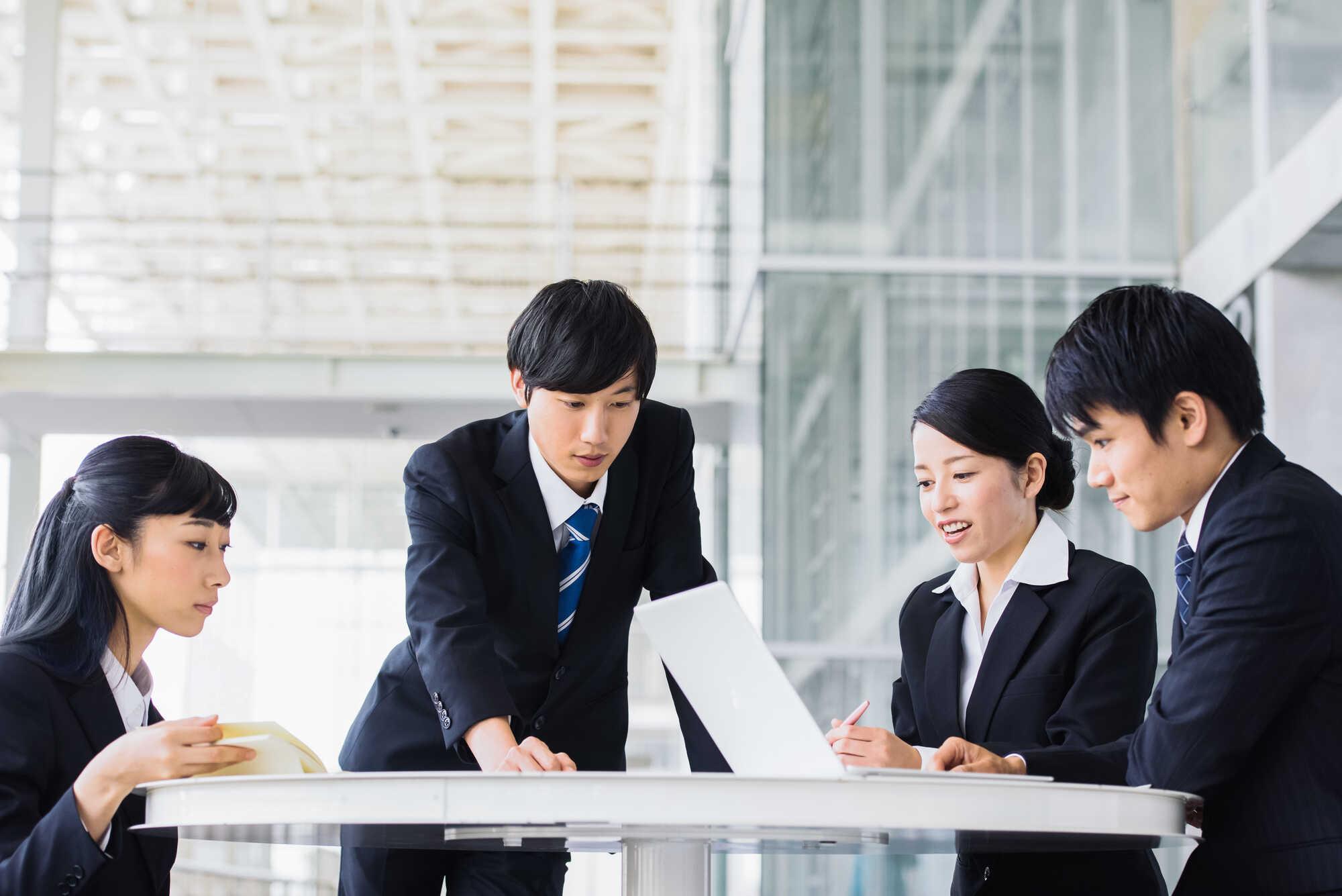 テーブルを囲んでいる若いビジネスパーソンたち