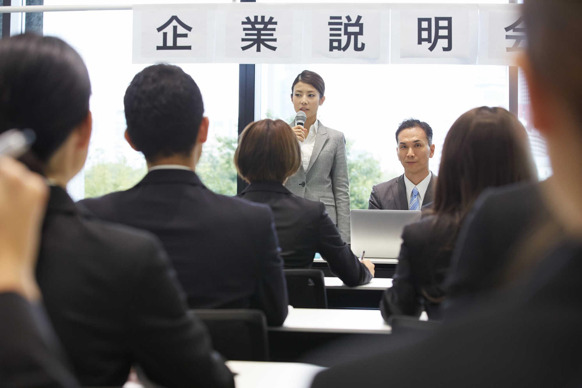 企業説明会の会場で話をしている女性