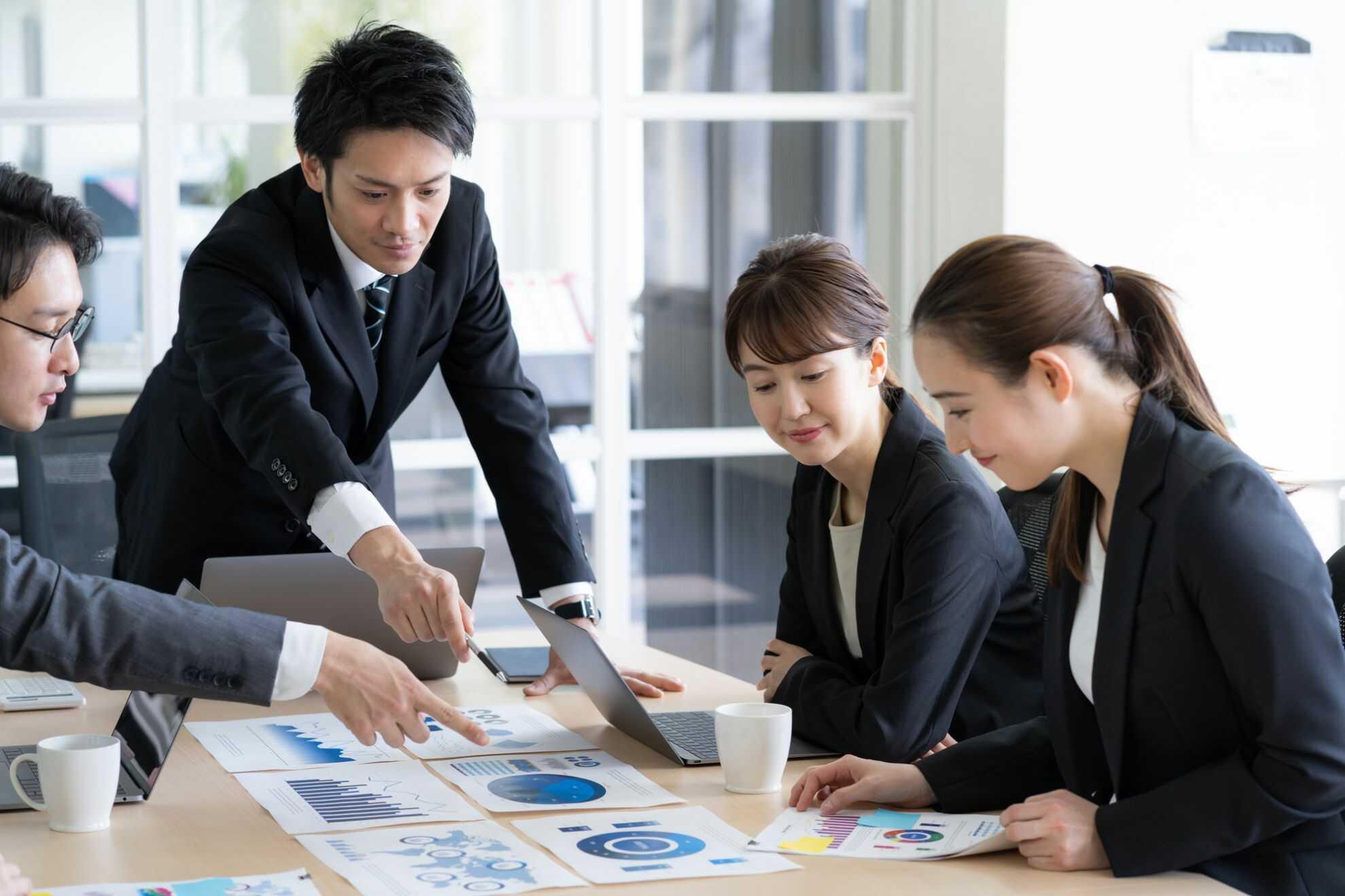 机の上に並んだグラフを見て打ち合わせ中のビジネスパーソン