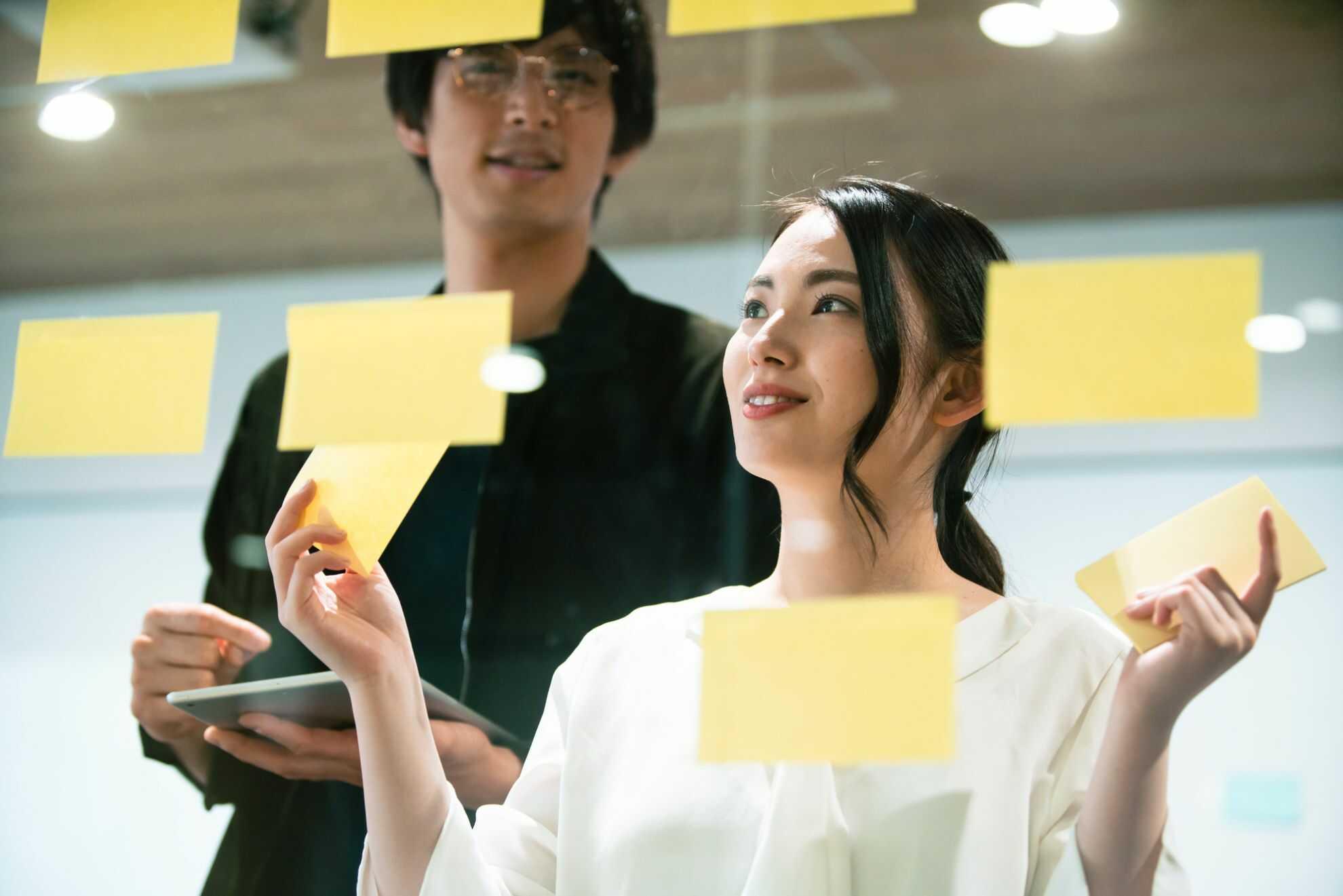 付箋を使って会議で出た意見を整理する女性