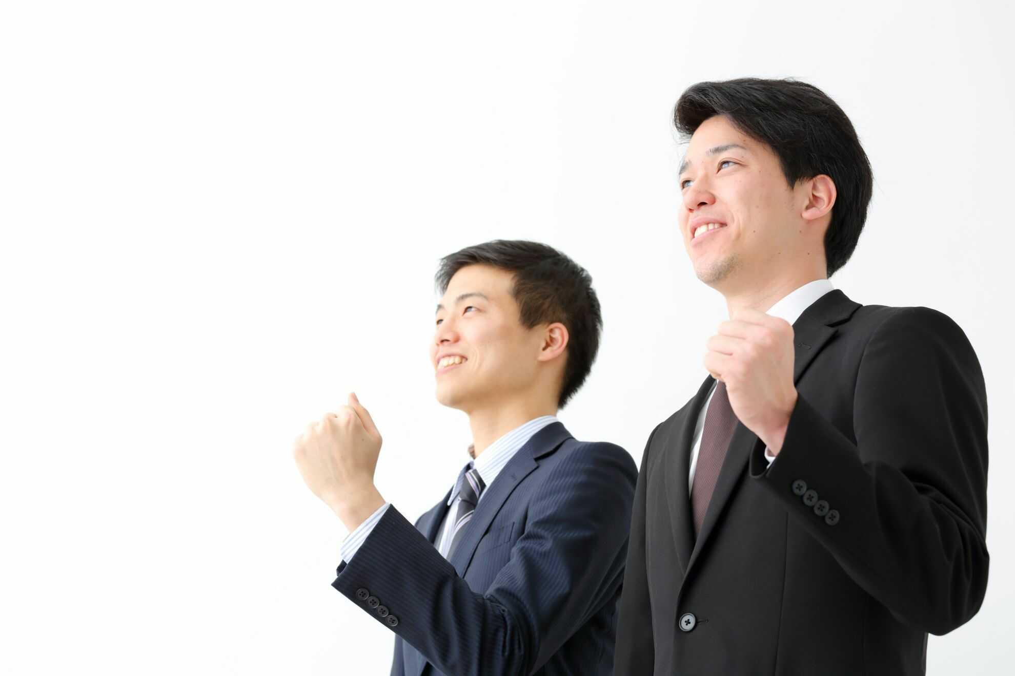 こぶしを握って前を見ている2人の男性