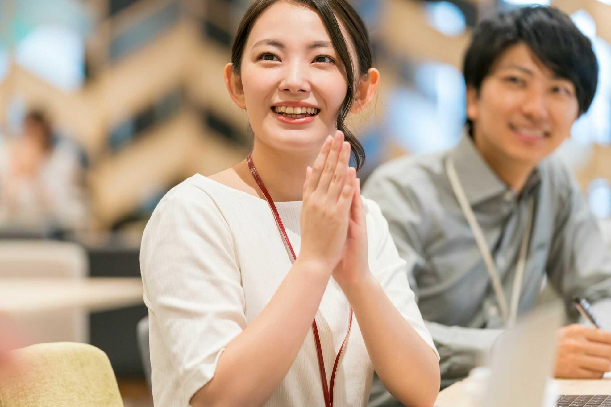 顔の前で拍手をしている女性