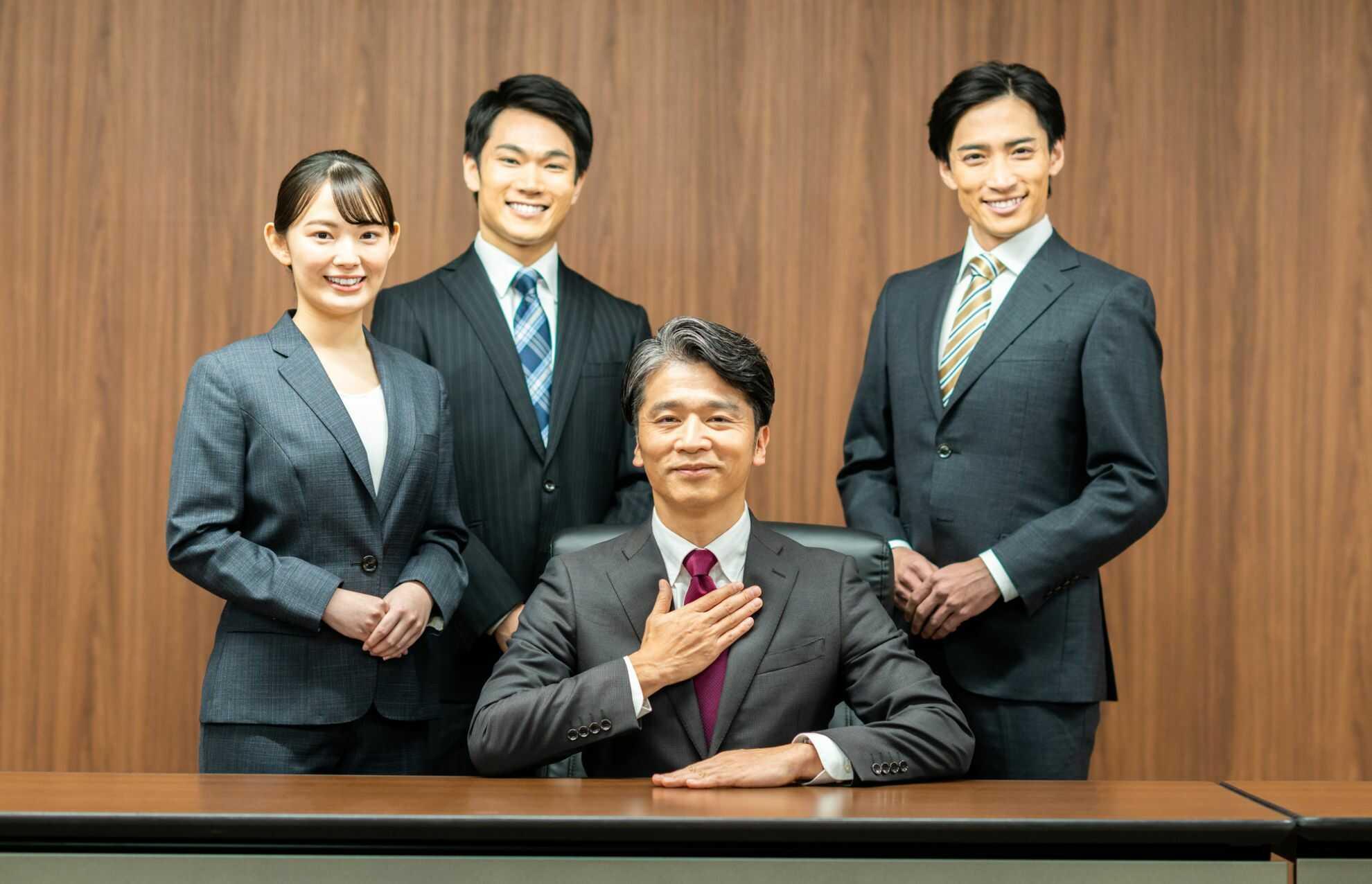椅子に座っている上司と、上司のそばに立っているメンバーたち