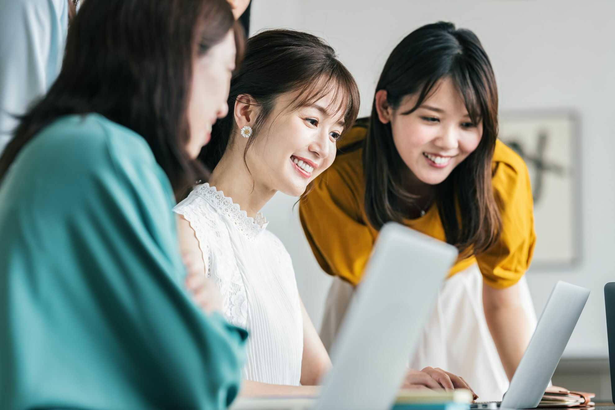ノートパソコンを見ながら談笑している3人の女性