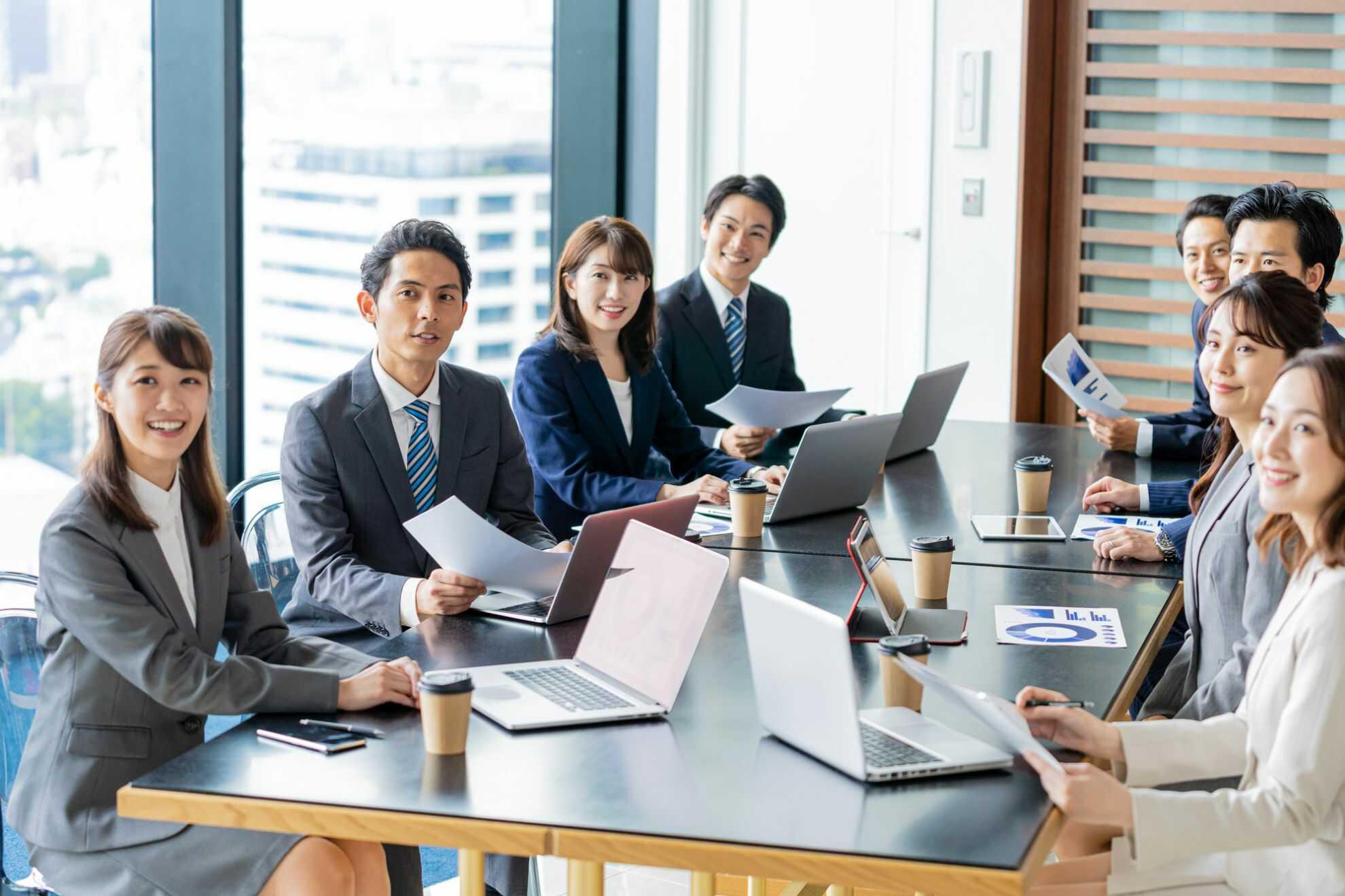 机に座ってこちらを見つめているビジネスパーソンたち
