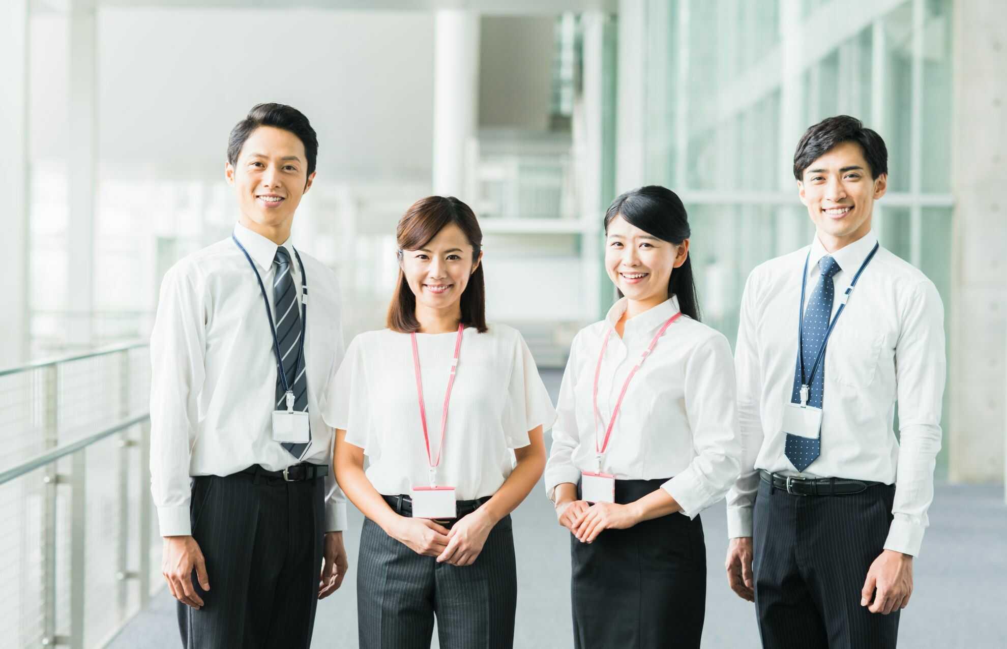 笑顔浮かべてこちらを見つめている4人のビジネスパーソン
