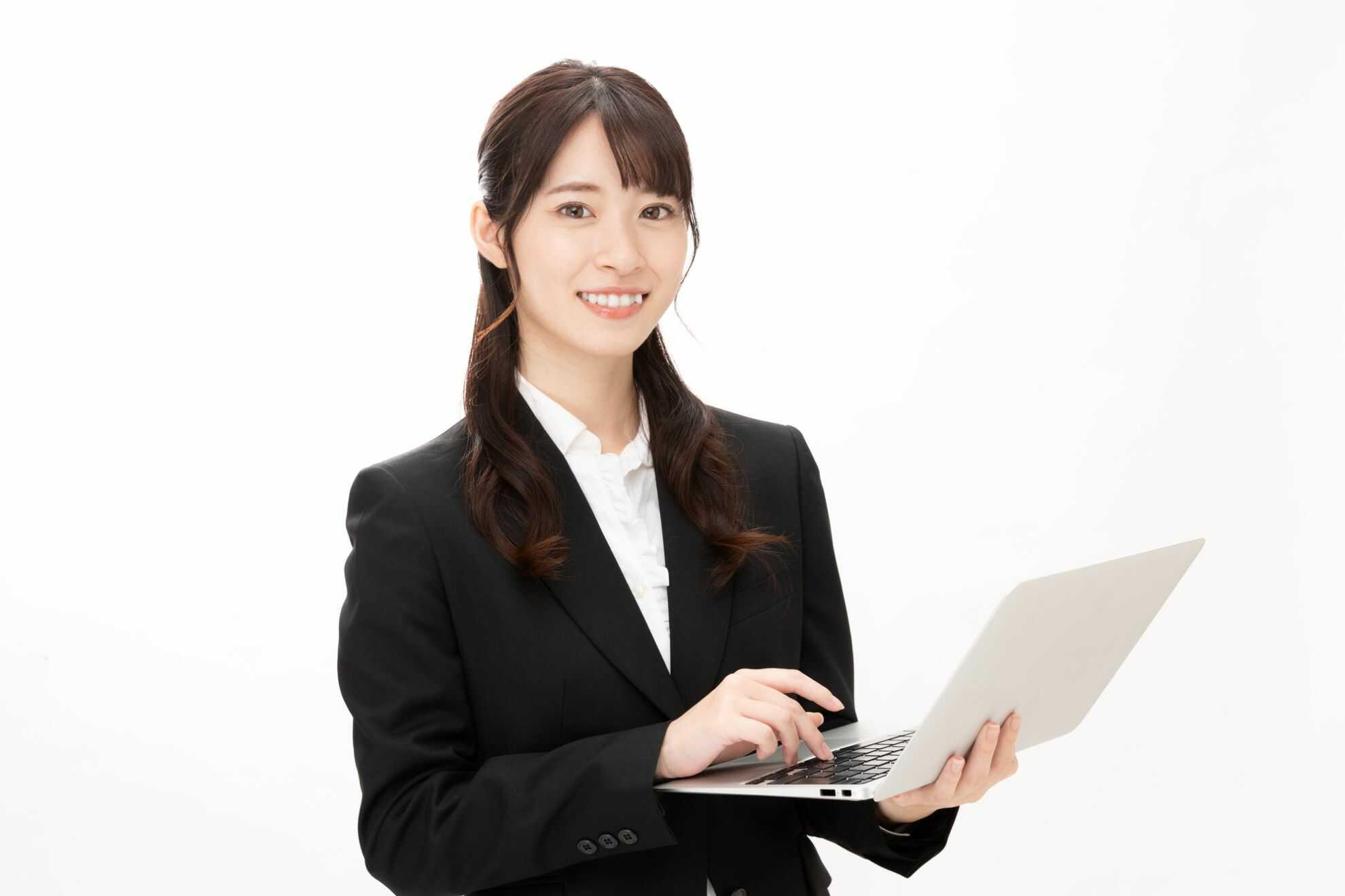 ノートパソコンを片手にこちらを見つめている女性