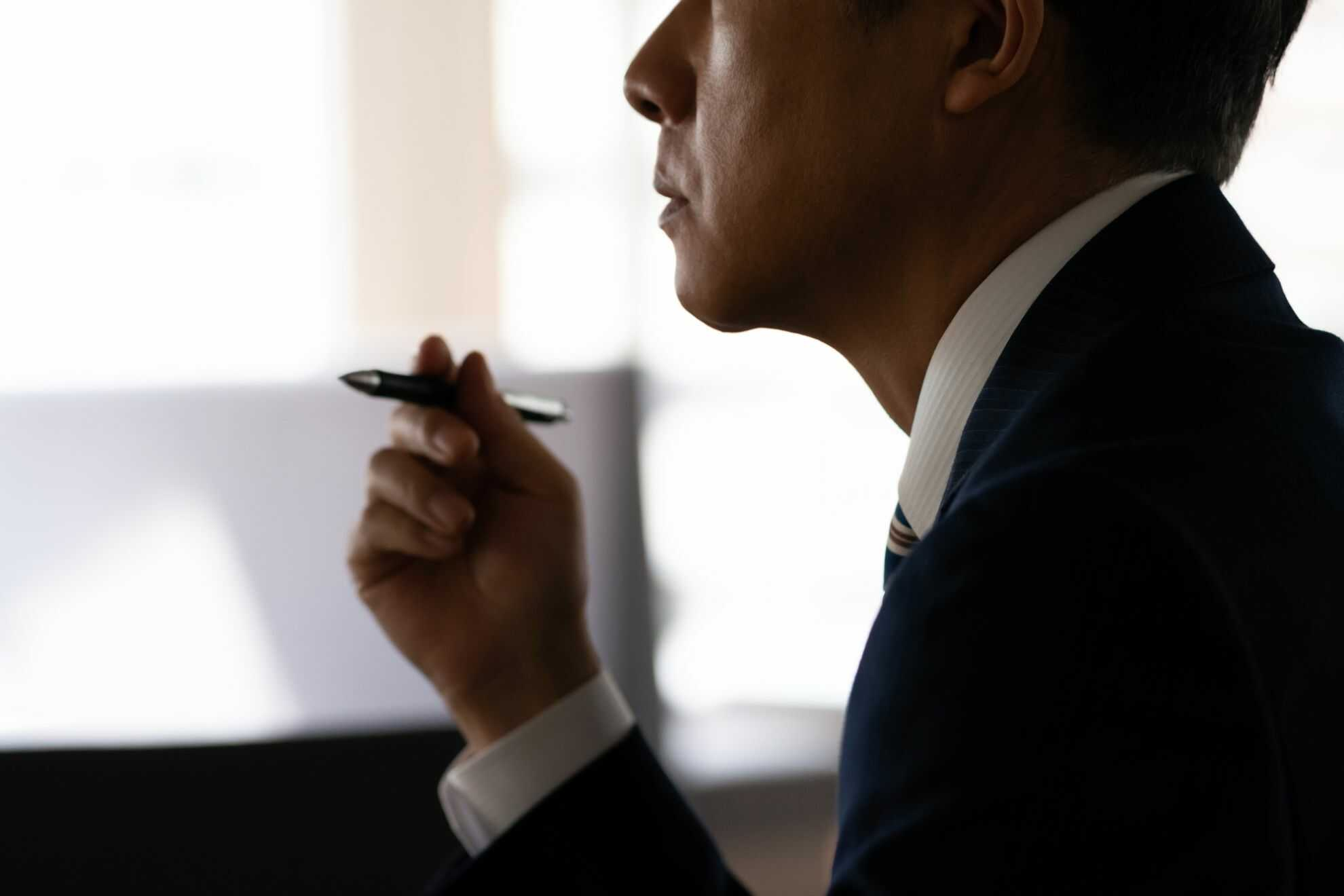 ペンを回しながら真剣な表情をしている男性
