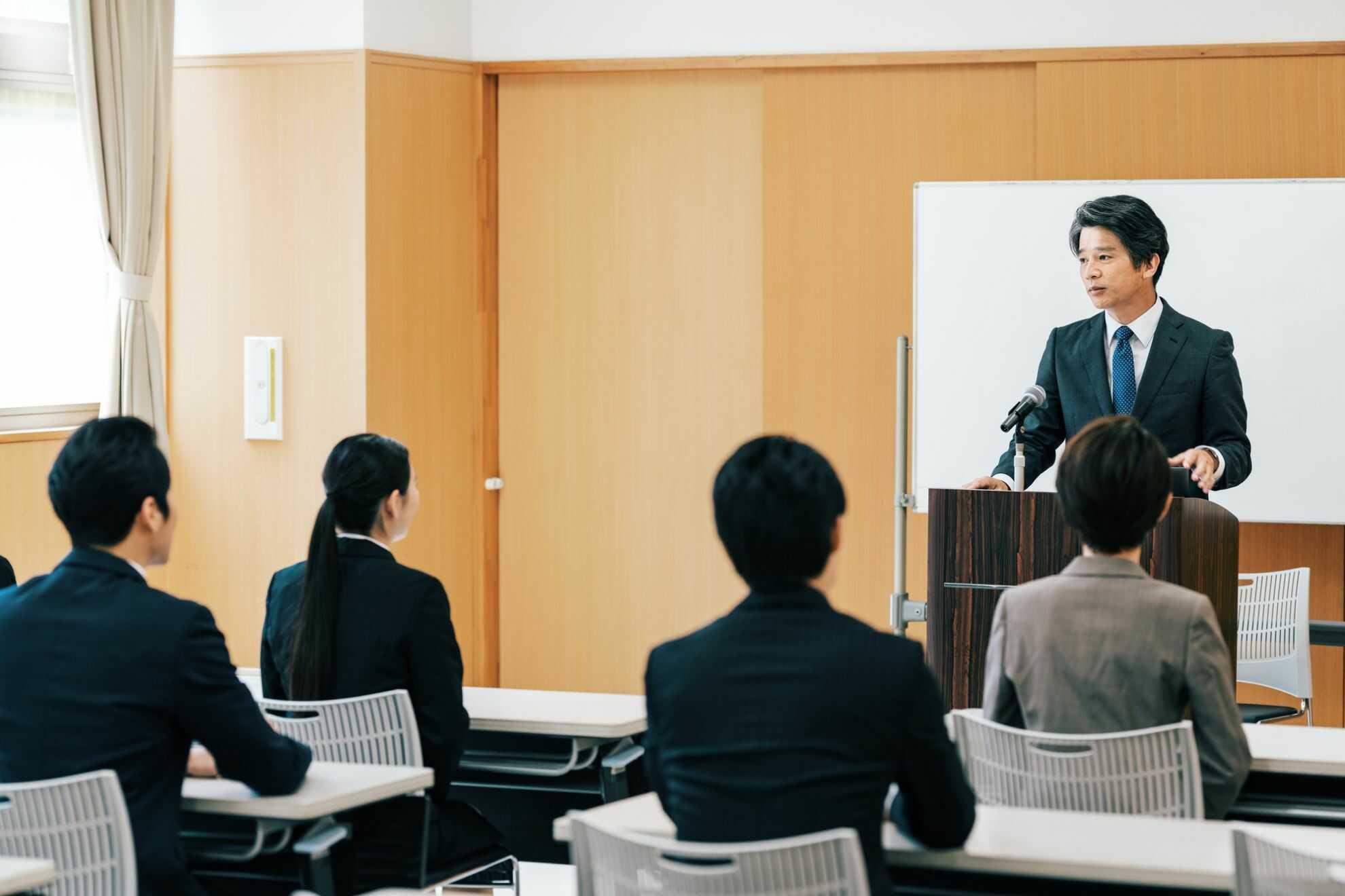 講義中の研修講師と手前の列にいる受講者