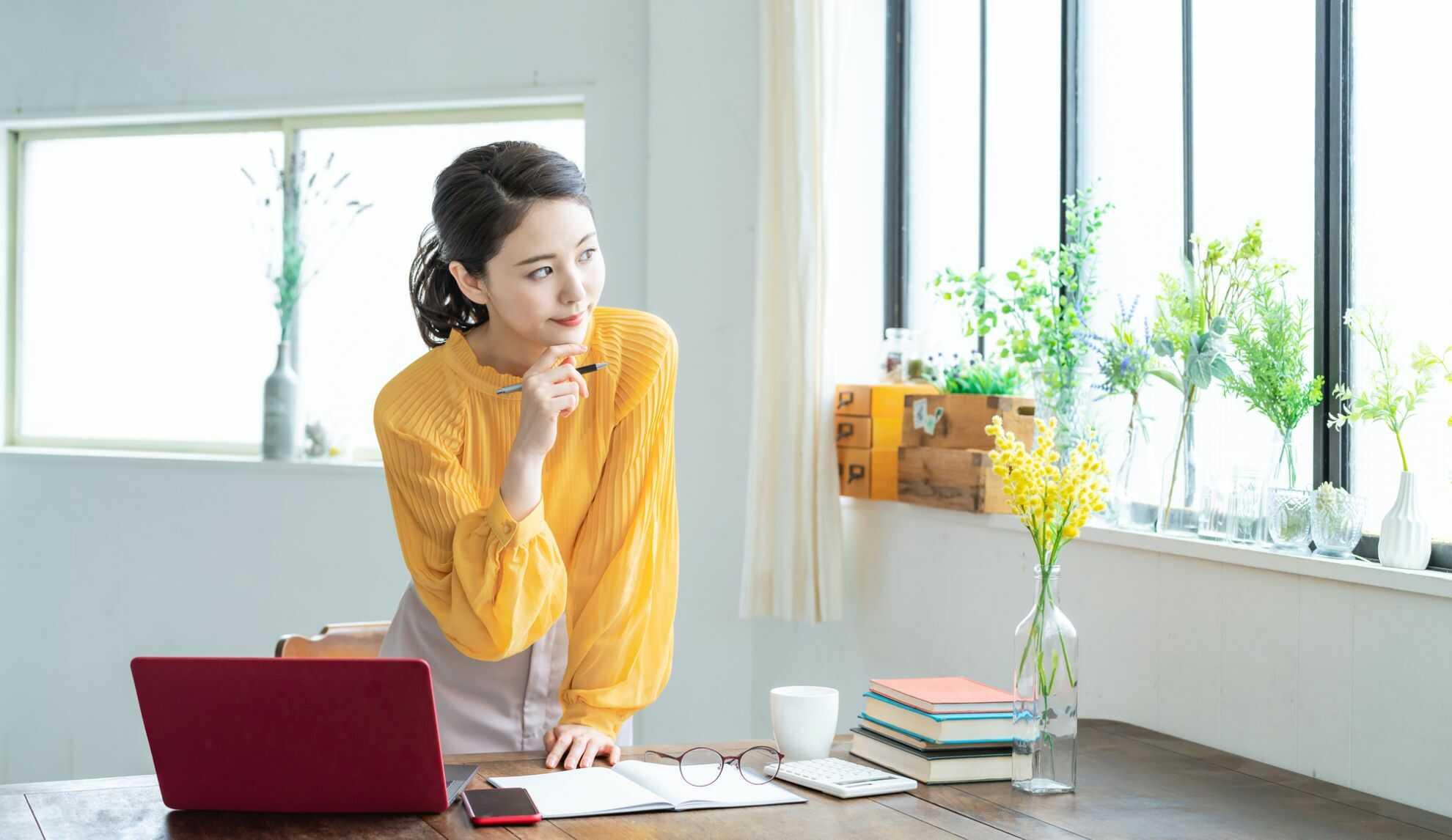 机に片手を突いて窓の外を見つめている女性