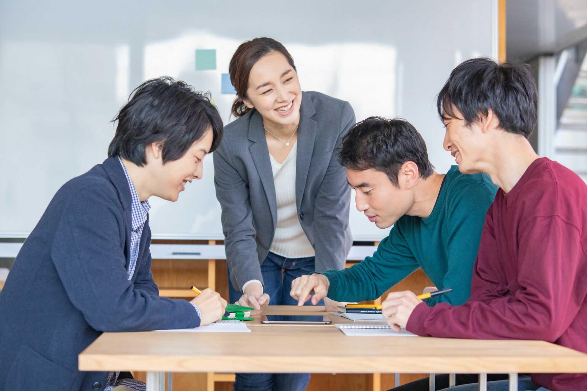 机を囲んで談笑している男女