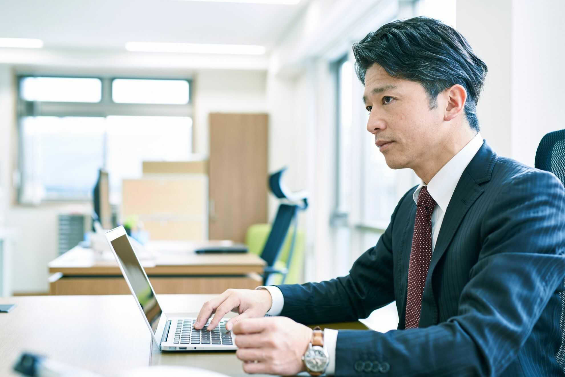 ノートパソコンを開いて前を見ている男性