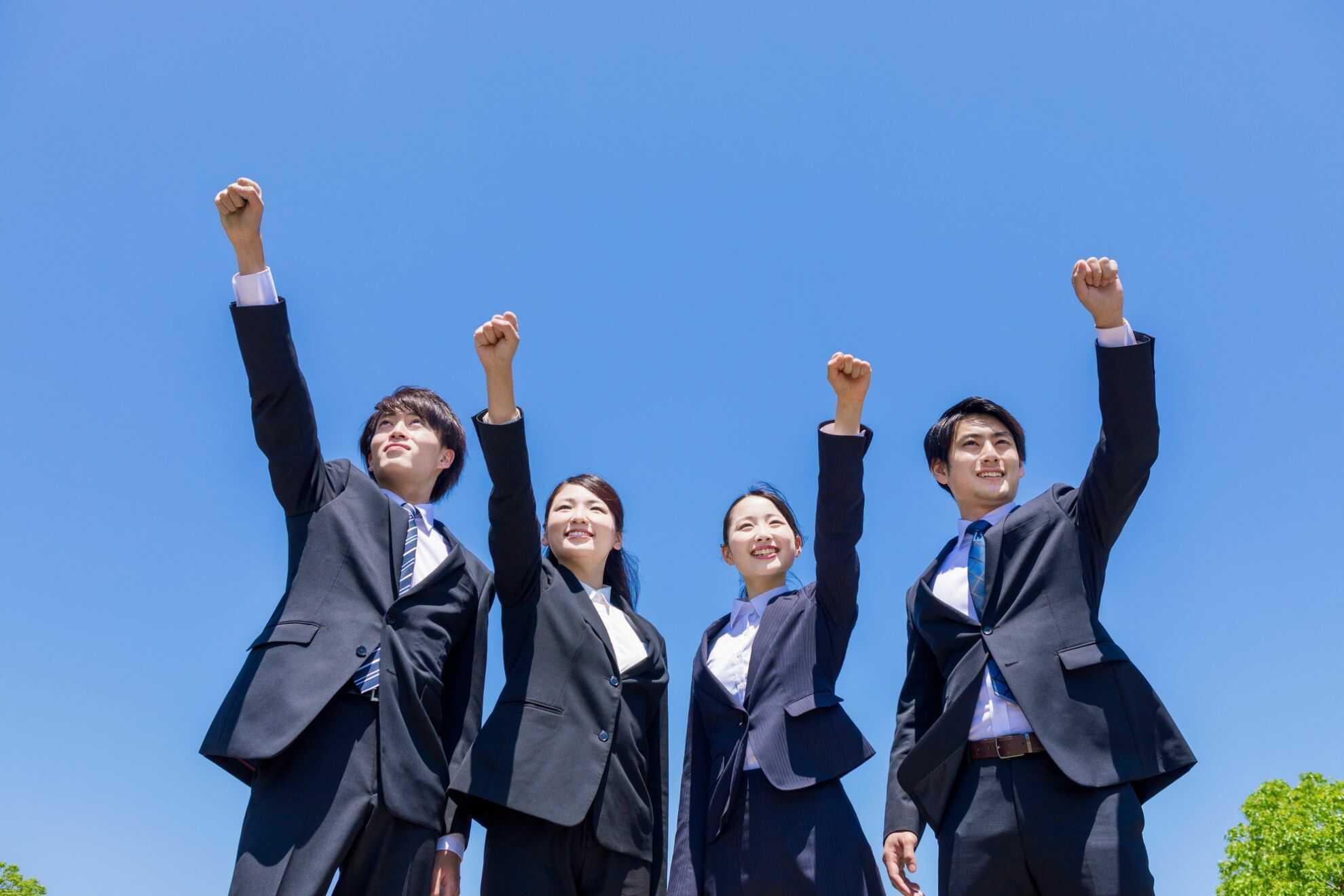 こぶしを掲げて立っている4人のビジネスパーソン