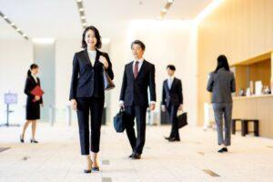 企業のエントランスにいるスーツ姿のビジネスパーソン