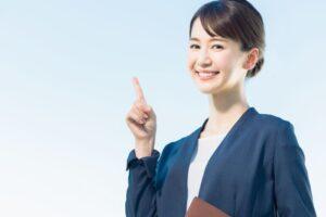 笑顔で人差し指を掲げる女性
