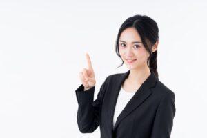人差し指を掲げる女性社員